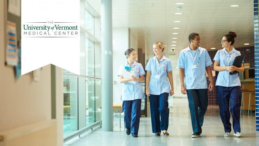 a group of four young trainee nurses including male and female nurses , walk towards camera down a hospital corridor .