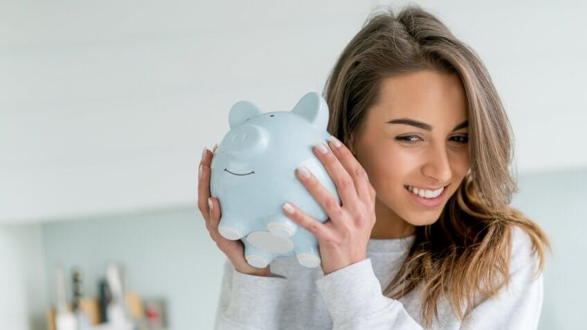 Happy young woman saving money in a piggybank - home finances concepts.