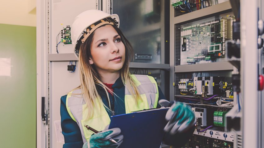 Young woman industrial service engineer wearing white worker headwear standing, working, checking conducts a safety check front of a control panel read and writing notes about technical problems in boiler energy control room of modern thermal or nuclear power plant electric energy station.