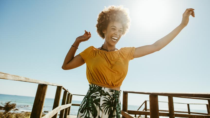 Excited young woman running on a boardwalk with her hands raised on a sunny day.