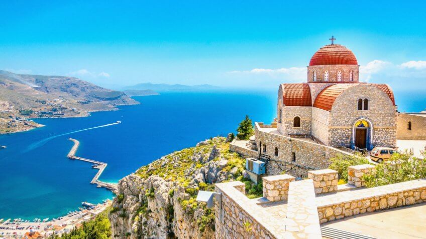 Amazing view on remote church with red roofing on the Cliff of the sea, Greece.