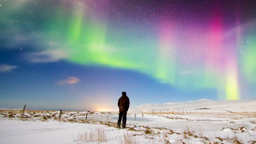 Man looking at Aurora Borealis in north Iceland.