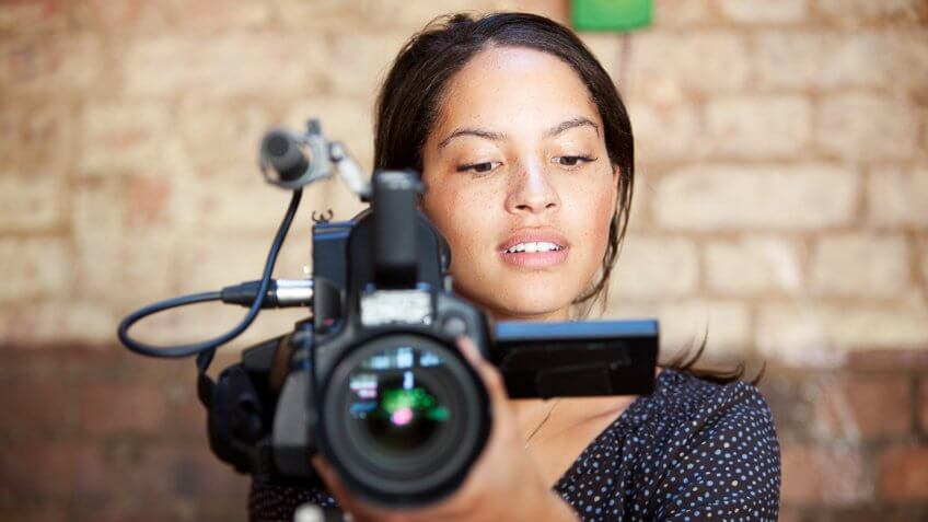 A look of content concentration on the face of a camera operator pleased with the results of her shoot.