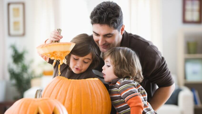 Mixed race father and sons carving Halloween pumpkins.