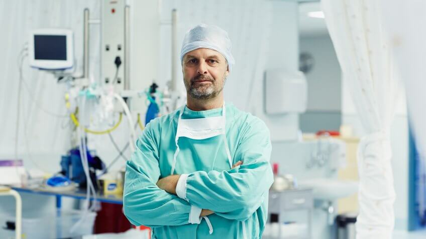 Portrait of confident male surgeon standing arms crossed in operating room at hospital.
