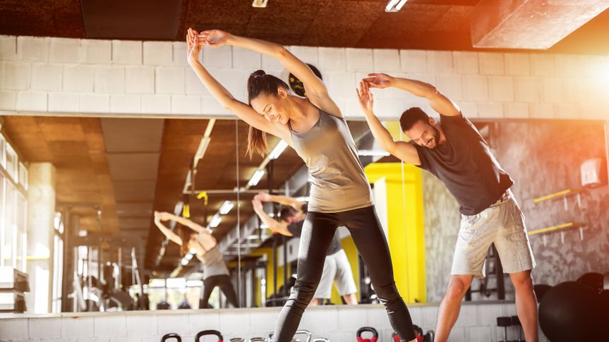 man and woman stretching, workout-gym