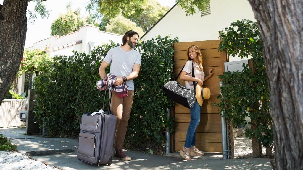 Couple with luggage arriving at vacation house gate.