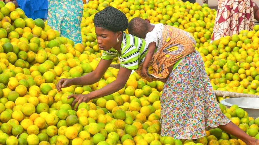 Esiam, Ghana - July 26, 2010: People picking oranges at the market in a small city Esiam near to the border between Ghana and Ivory Coast.