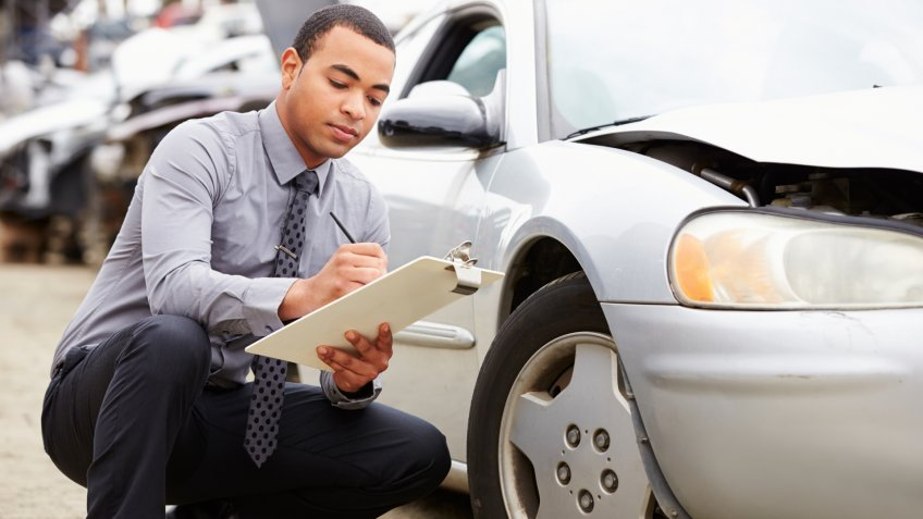 Loss Adjuster Inspecting Car Involved In Accident Crouching Down.