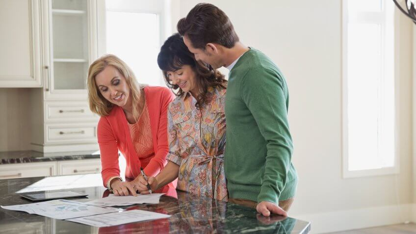 Female realtor discussing documents with couple.