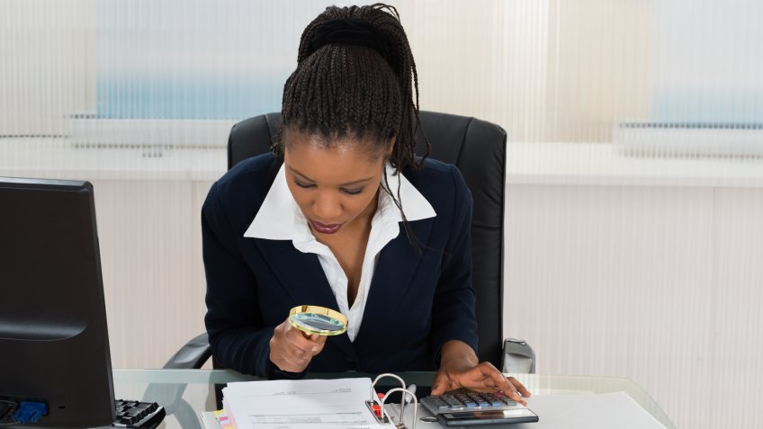 African Businesswoman Looking At Invoice Through Magnifying Glass.