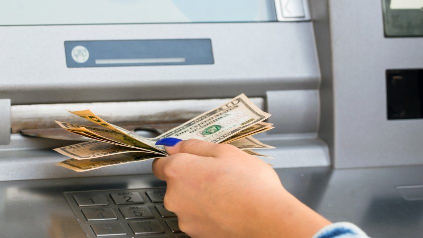 withdrawing money from outdoor bank ATM