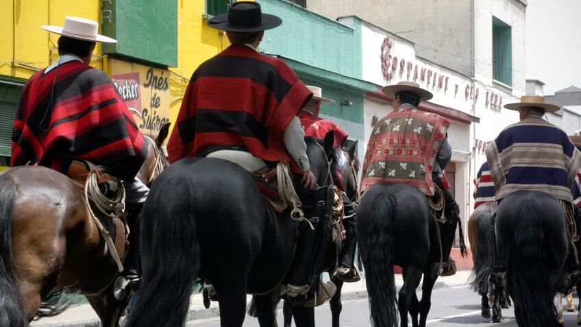 Santiago, Chile - December, 6th 2004: Gaucho's cowboys in traditional ponchos ride through the streets of the Chilean capital as part of a street fiesta.