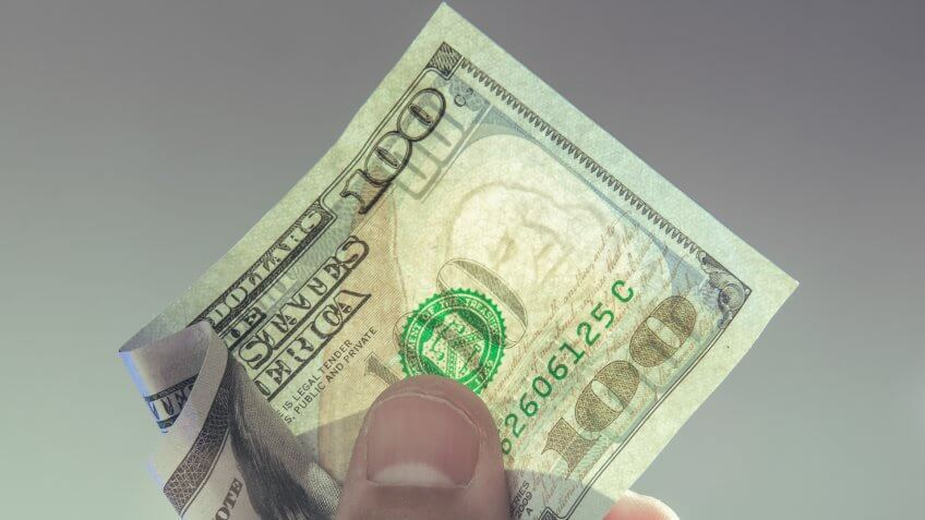 A hand holding a one hundred dollar bill with translucent Franklin watermark visible.