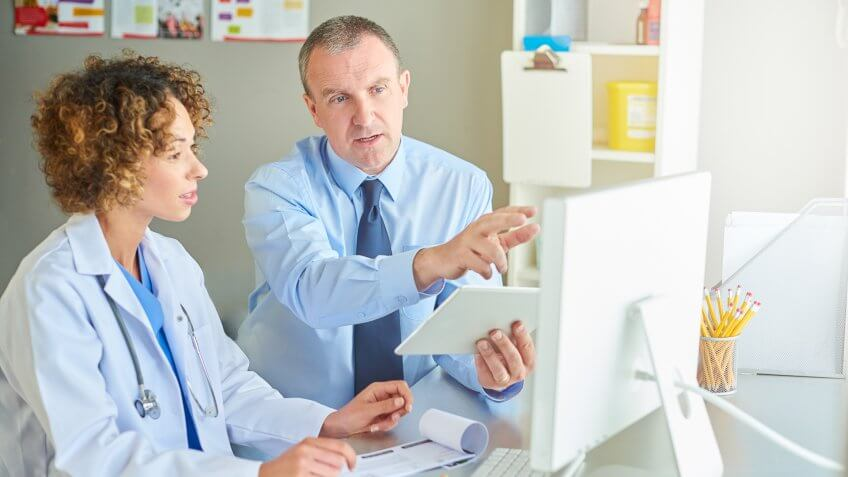a medical salesman or administrator is sitting with a female doctor and running through a presentation .