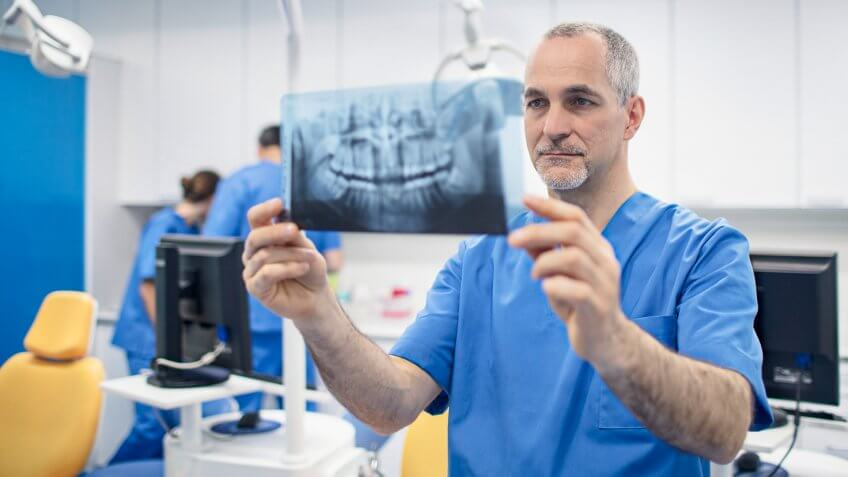 Mature male orthodontist looking at X-ray image.