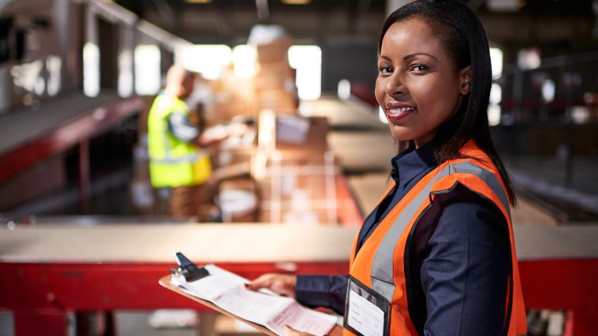 Portrait of a warehouse manager holding a clipboard with workers in the background.