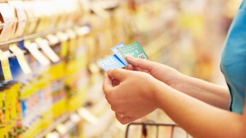 Woman In Grocery Aisle Of Supermarket With Coupons.