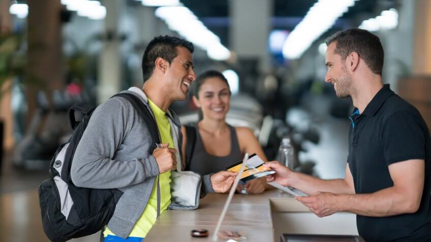 Happy couple of people at the gym talking to the receptionist about membership plans - healthy lifestyle concepts.