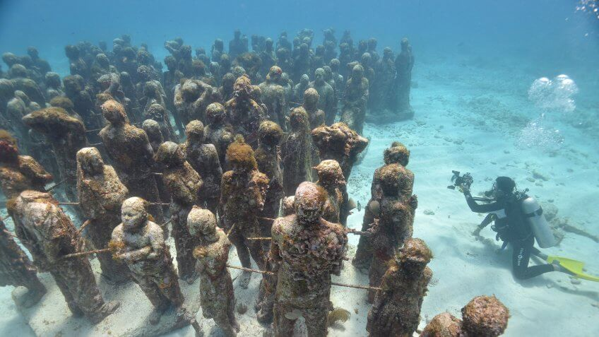 High angle view scuba diver photographing Cancuns underwater statues, Isla Mujeres, Quintana Roo, Mexico.