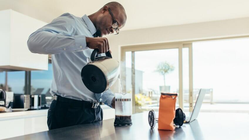 Man pouring hot water in coffee maker.