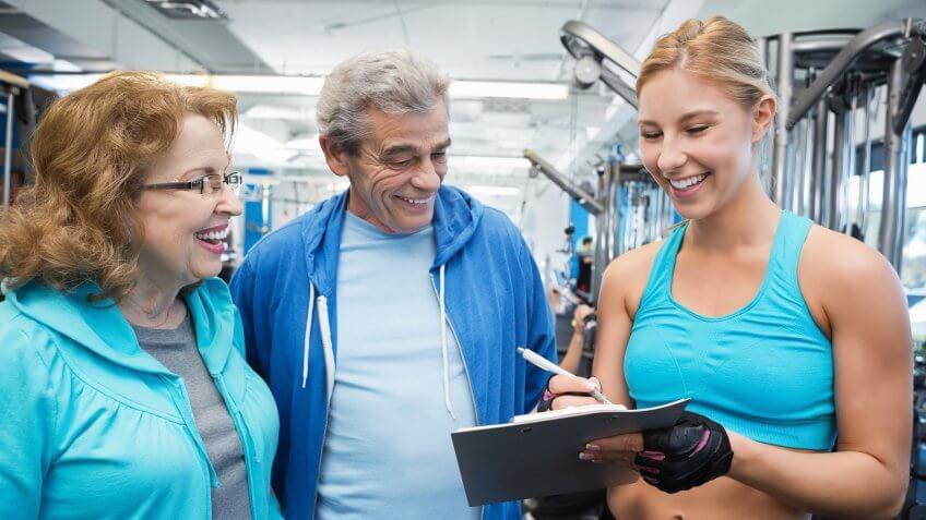 Gym trainer giving senior couple membership information.