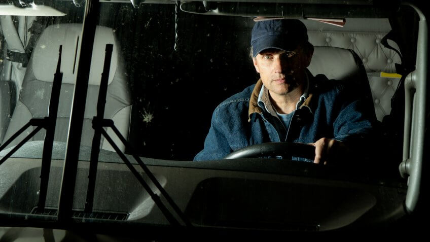 A long haul truck driver in his semi lit up by oncoming headlights.