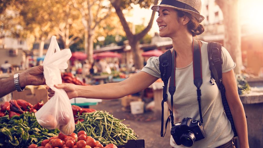 Shot of a woman buying fruit and vegetables at a market in a foreign cityhttp://195.