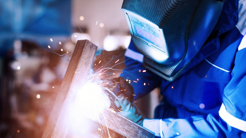 Blue collar worker or engineer working in industrial production plant, dealing with metal processing, hydraulic machinery, production lines and other pprocessing industry machines.