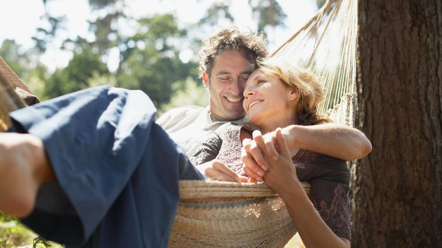 Couple sitting in hammock.