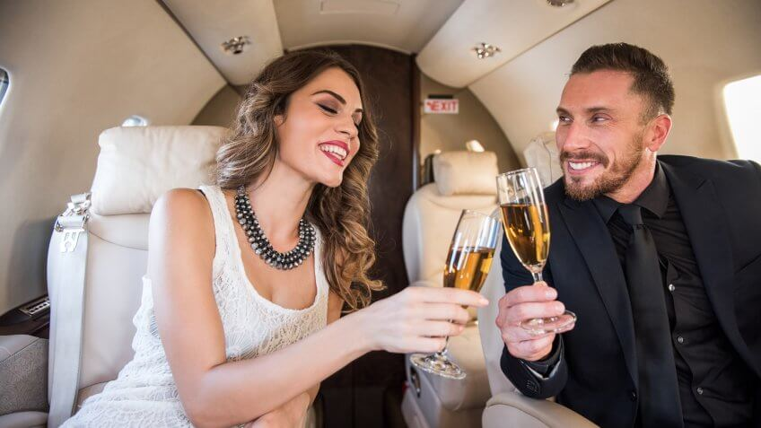 Business couple sitting inside private jet airplane and having a champagne toast.