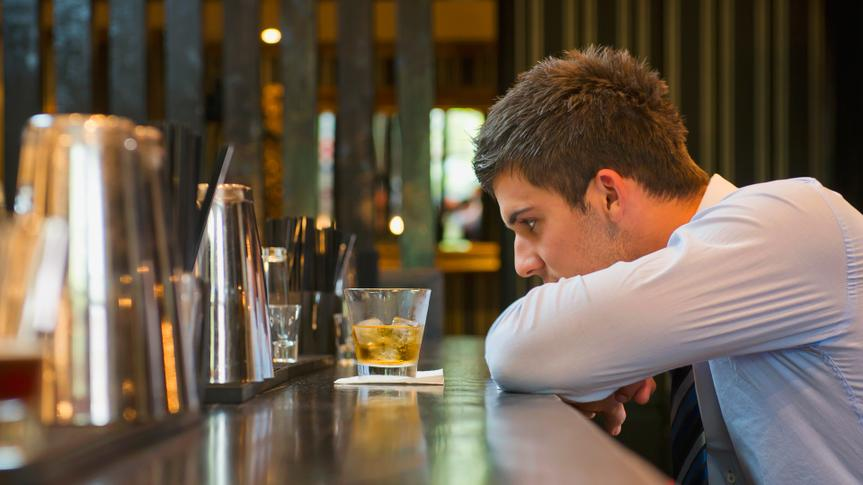 Lonely Hispanic businessman sitting at bar.