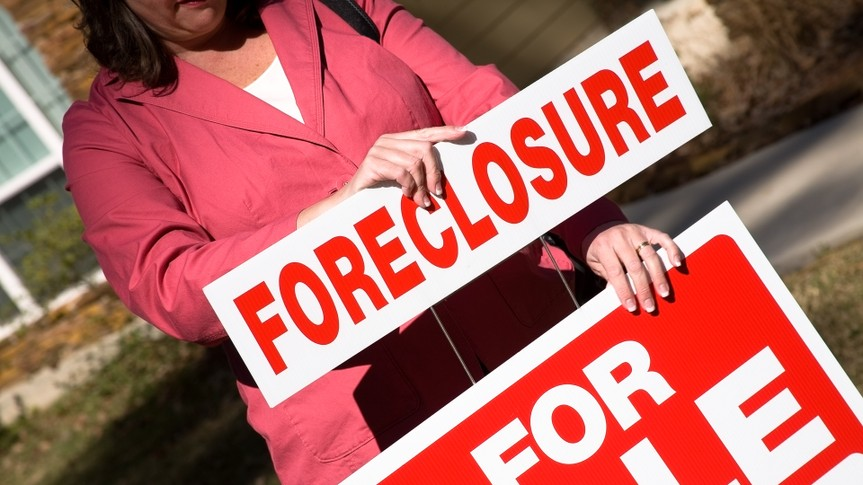 Realtor placing a foreclosure sign on the for sale sign in front of a home.