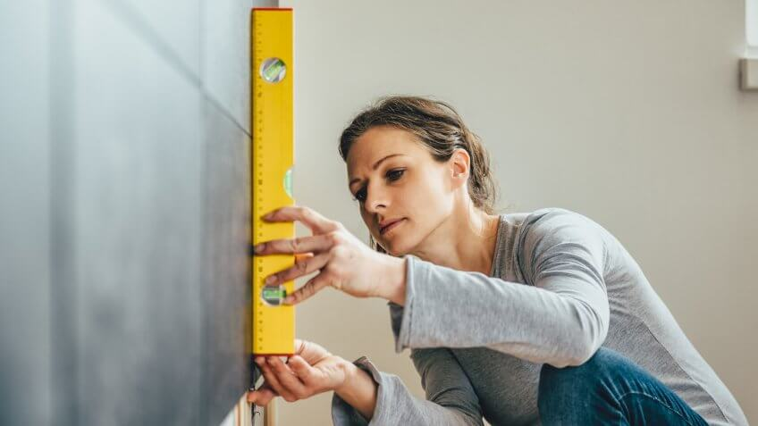 Woman wearing grey shirt using leveling tool at home.