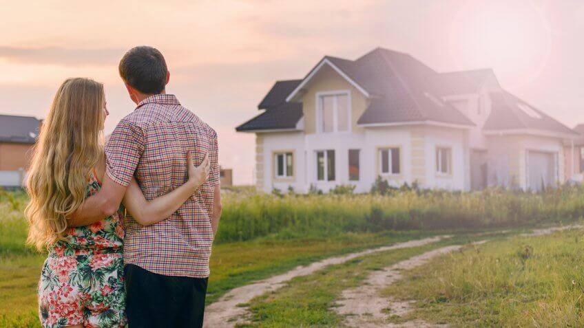 Young Couple Standing Outside Dream Home.