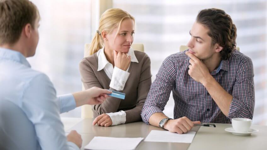 Young serious couple thinking over high housing costs, rent levels and security of tenancy, trying to buy a home with a minimal down payment, calculating monthly budget, pay with card.