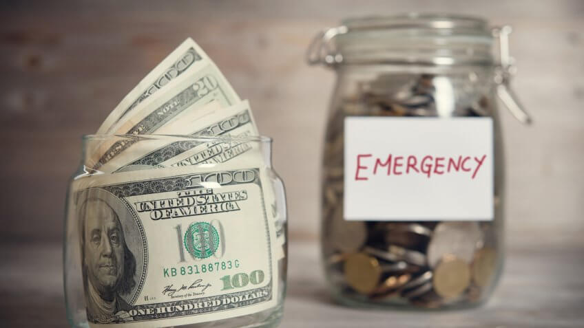 Dollars and coins in glass jar with emergency label, financial concept.