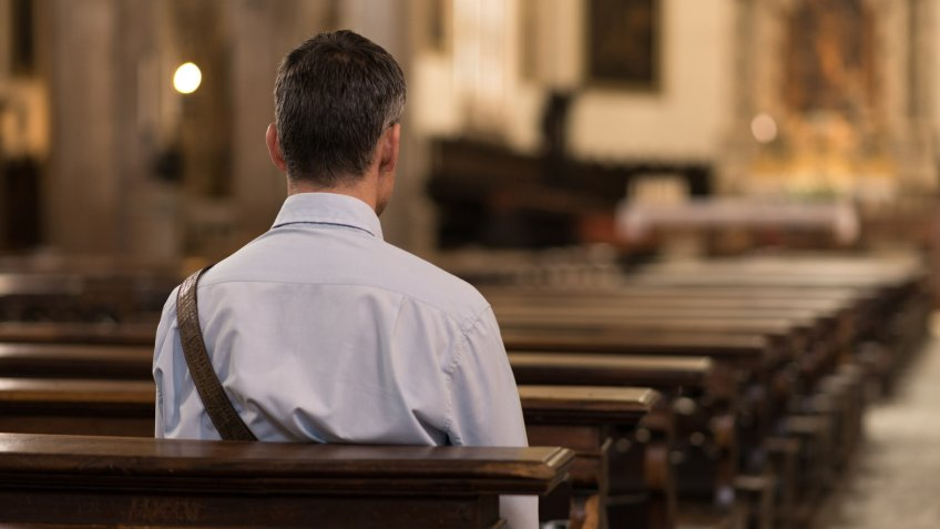 Man sitting in a pew at Church and meditating, faith and religion concept.