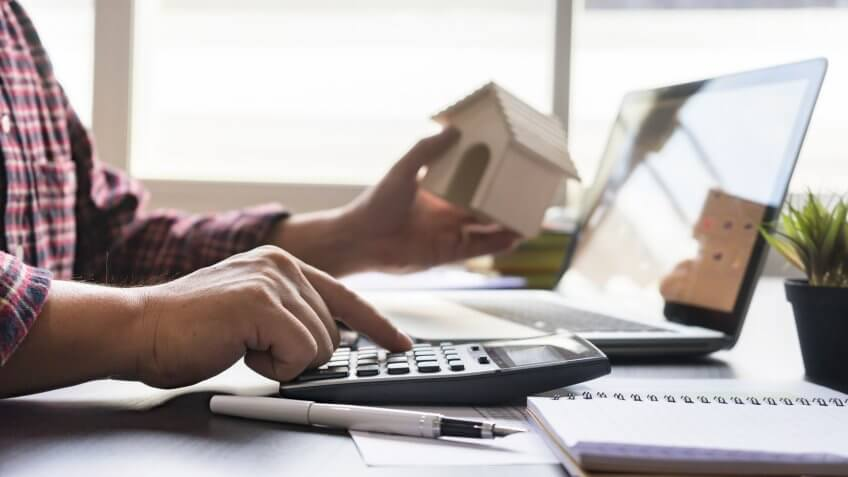 Businessman bookkeeper or financial inspector hands making report, calculating or checking balance on calculator.