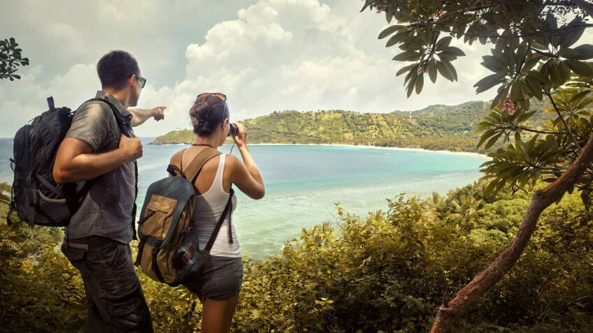 Tourist couple with backpacks enjoying views coast island Lombok.