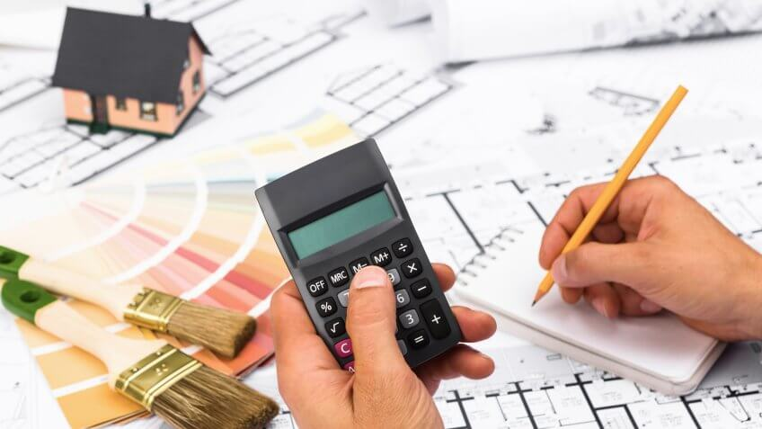businessman working on accounts using a calculator and writing on notebook.