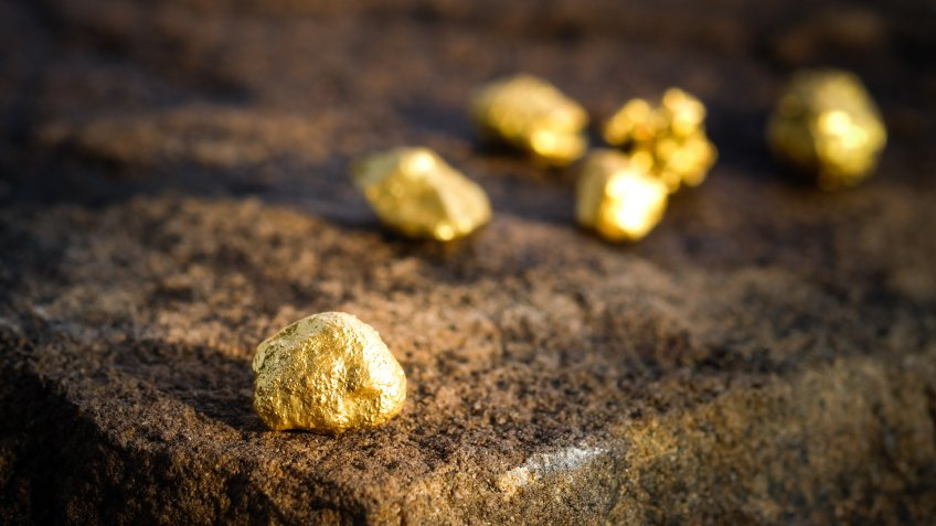 The pure gold ore found in the mine on a stone floor.