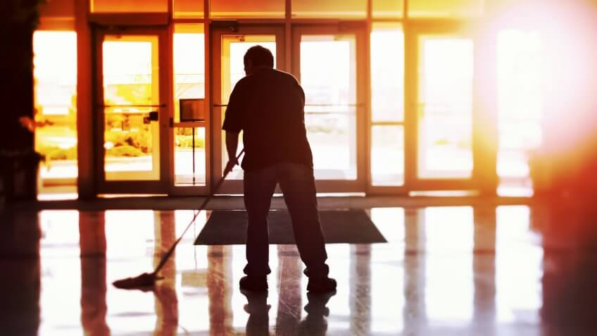 Janitor mopping an office floor, shallow focus, tilt shift image.