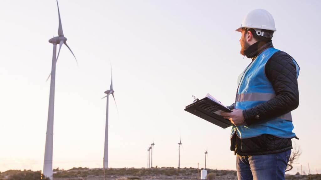 Young Handsome Beard Male Engineer in Wind Mill Power Generator Station with white safety hat and wind turbines on background.