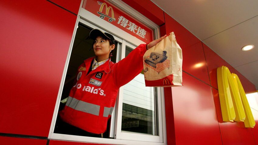 BEIJING - JANUARY 19:  A McDonald's employee hands out food as she waits on customers at their new drive-thru facility on January 19, 2007 in Beijing, China.