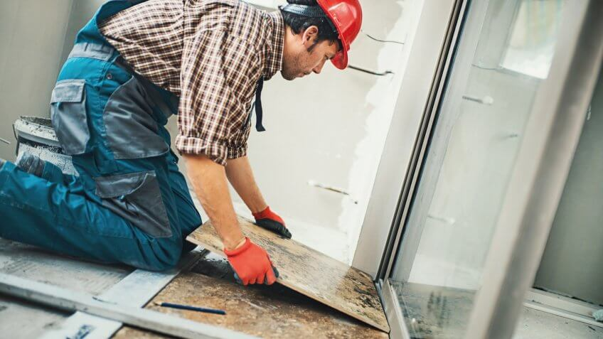 Closeup side view of a handyman installing green ceramic tiles over apartment floor.