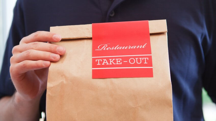 Close-up of an unidentifiable delivery man holding a take out food brown paper bag of restaurant dinner, delivering the fast food meal package.