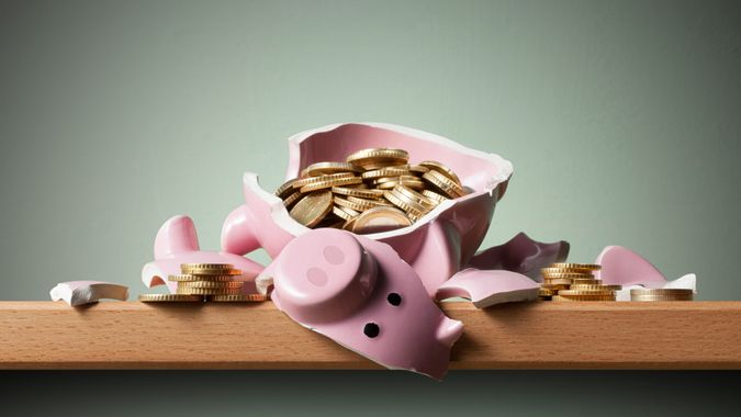 Broken piggy bank with euro coins on the shelf.