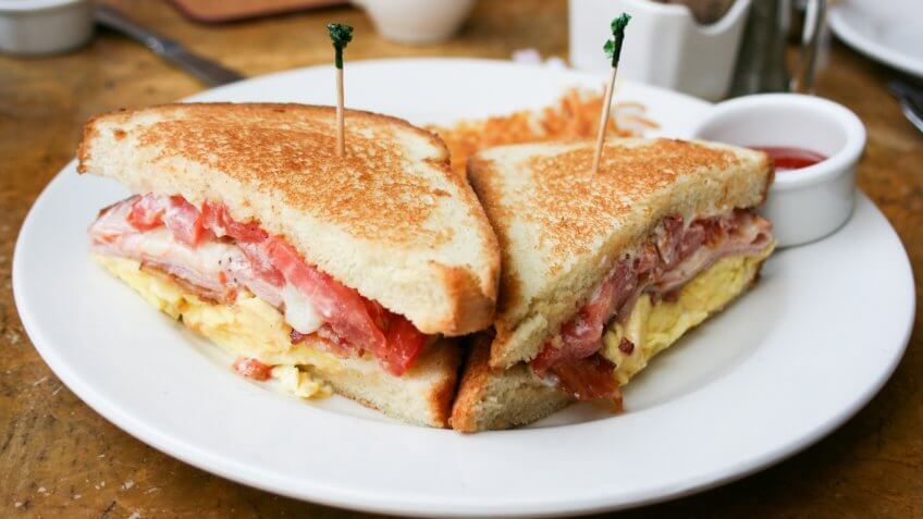 Eggs, bacon and cheese breakfast sandwich with hash brown potatoes, close up, lifestyle, horizontal.