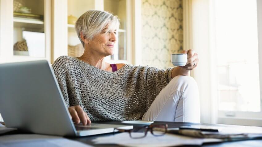 Pensive woman looking away drinking tea at laptop.